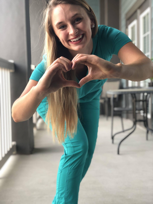 лекарка в униформа показва сърце с ръце